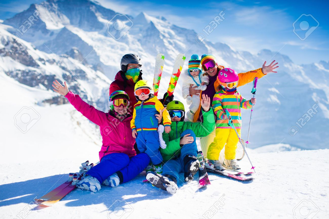 Family Ski Vacation Group Of Skiers In Swiss Alps Mountains Adults And Young Children