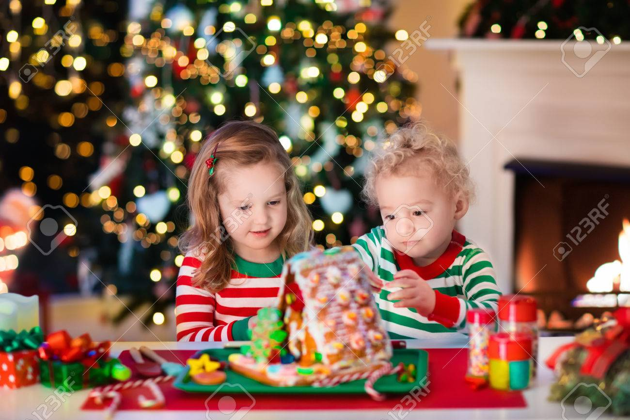 Little Boy And Girl Making Christmas Gingerbread House At Fireplace