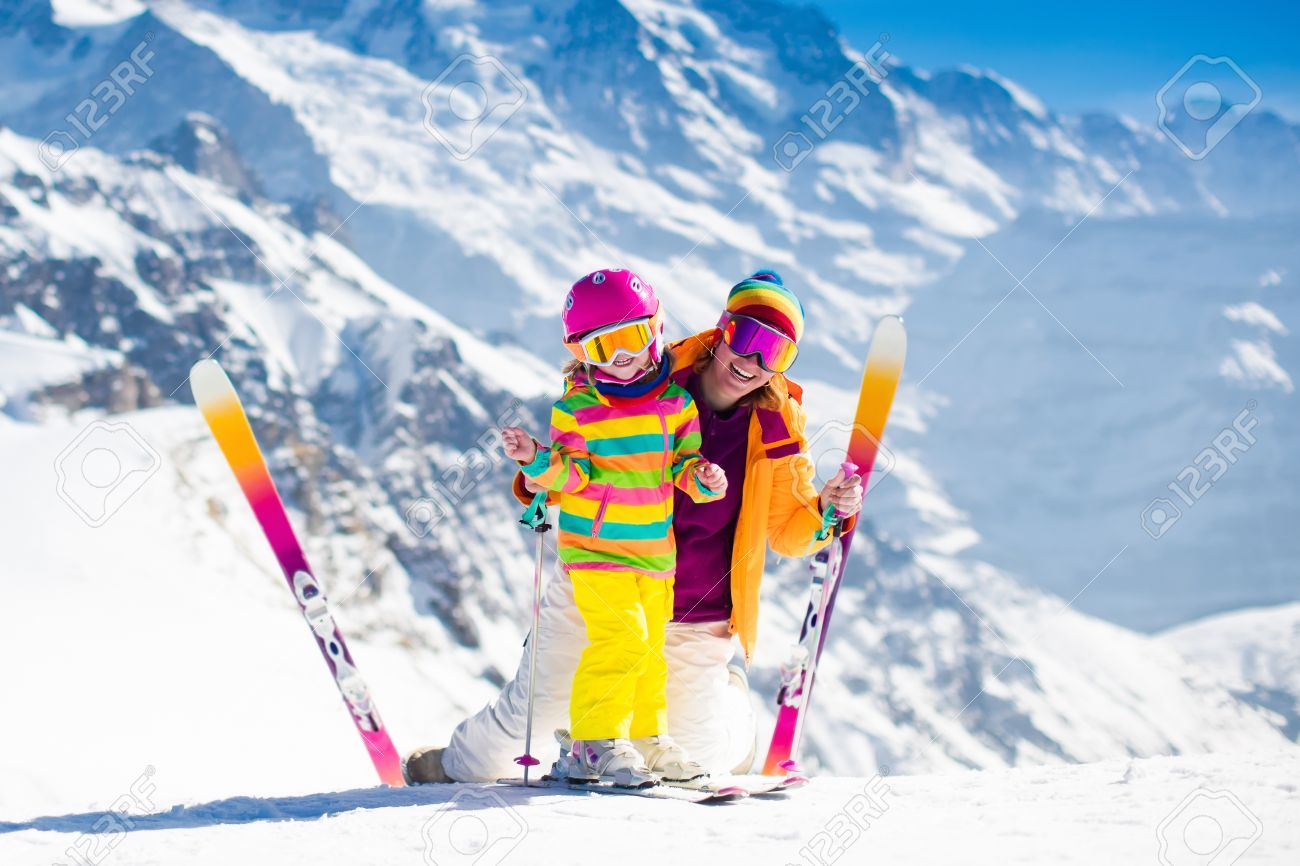 Family ski vacation. Group of skiers in Swiss Alps mountains. Mother and child skiing in winter. Parents teach kids alpine downhill skiing. Ski gear and wear, safe helmets. - 63589457