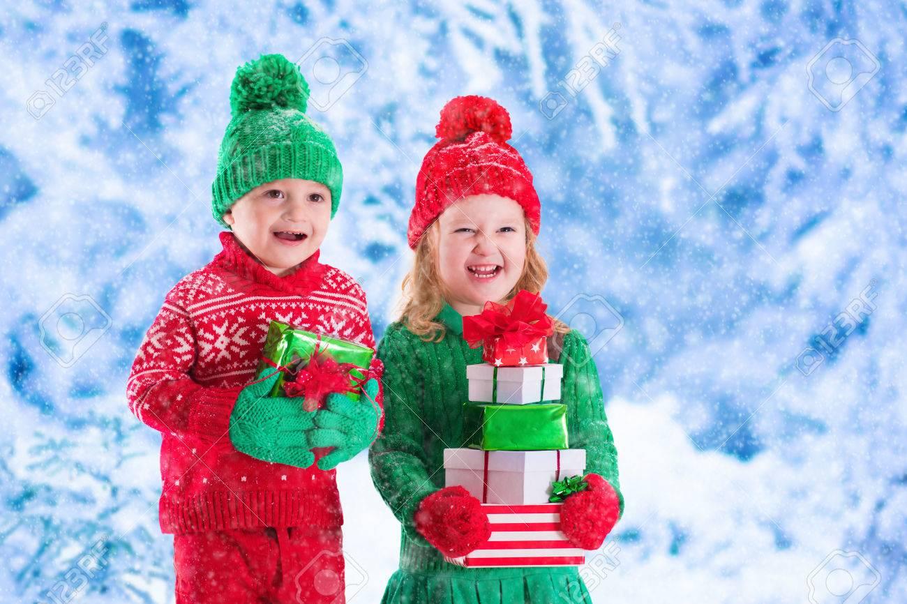Kleine Mädchen Und Jungen In Rot Und Grün Strickmütze Hält ...