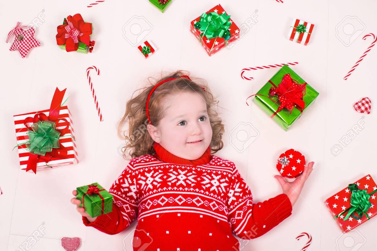 Kinderöffnung Weihnachtsgeschenke. Kleines Mädchen In Gestrickter ...