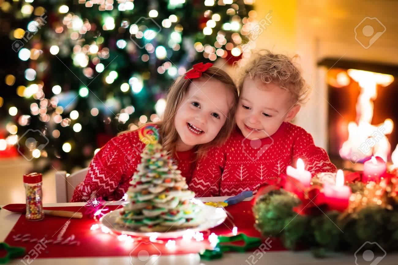 Kleiner Junge Und Mädchen, Das Weihnachtslebkuchenhaus Am Kamin In ...