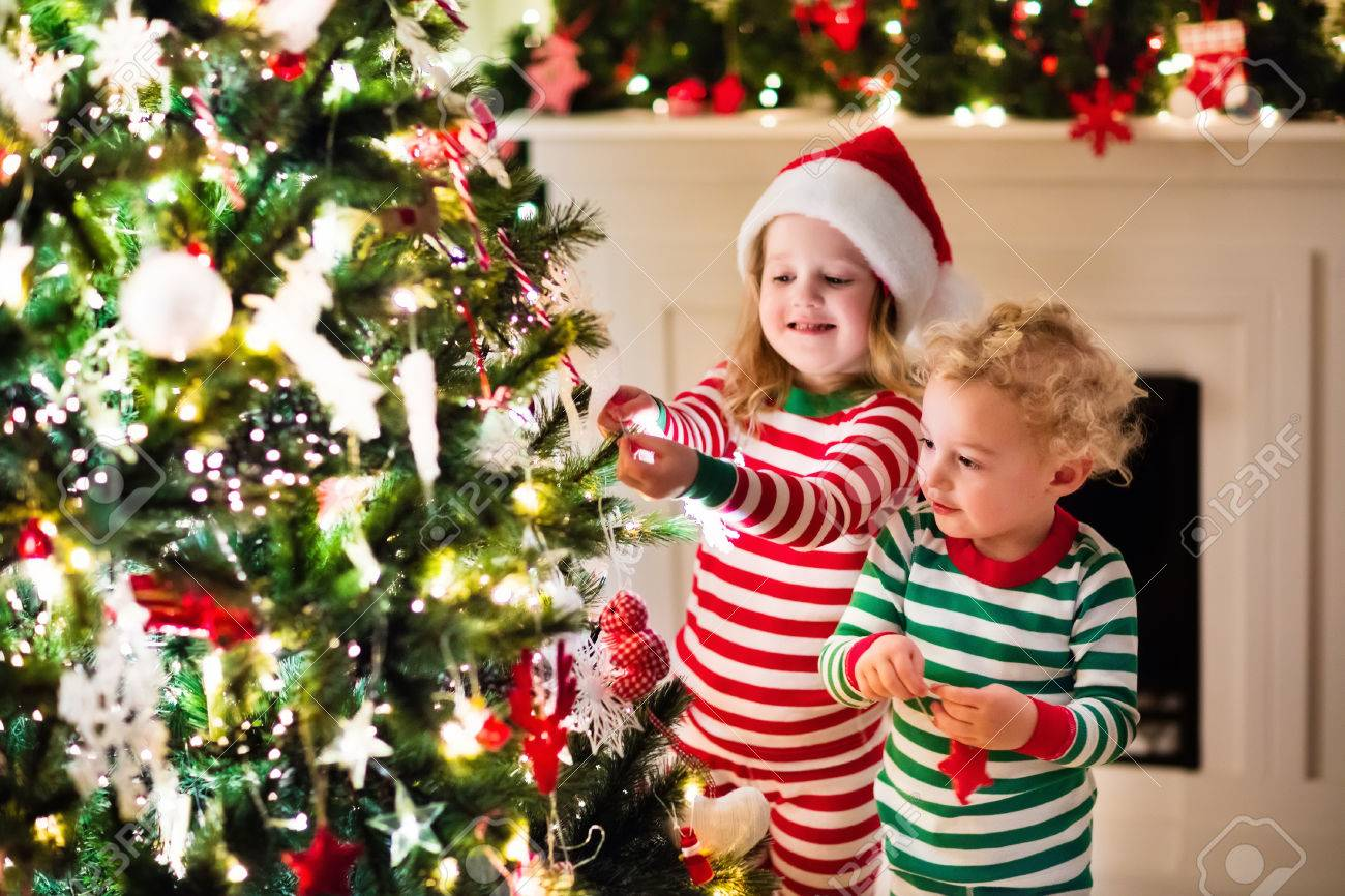 Happy Little Kids In Matching Red And Green Striped Pajamas Decorate ...