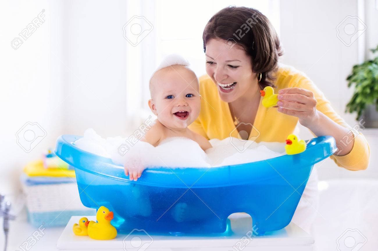 Happy baby taking a bath playing with foam bubbles. Mother washing..