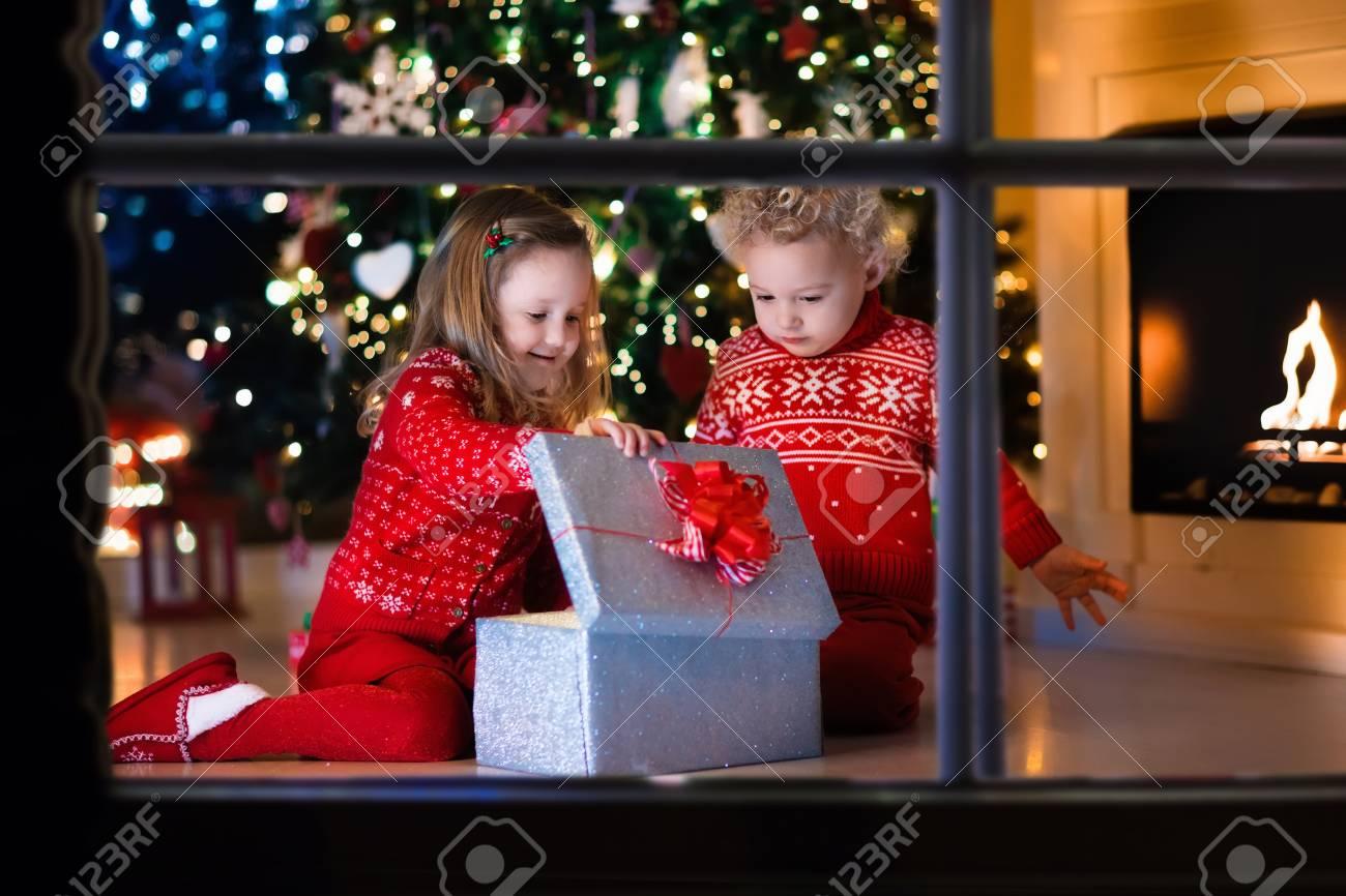 Regali Di Natale Famiglia.Famiglia Alla Vigilia Di Natale Al Camino Bambini Di Apertura Regali Di Natale I Bambini Sotto L Albero Di Natale Con Confezioni Regalo Decorato