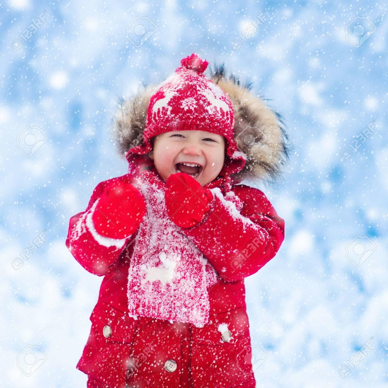 Bebé Que Juega Con Nieve En Invierno. Poco Muchacho Del Niño En La Chaqueta  Roja Y Renos De Navidad Sombrero Hecho La Captura De Copos De Nieve En El  Parque ... 8cf7a4ac5f8