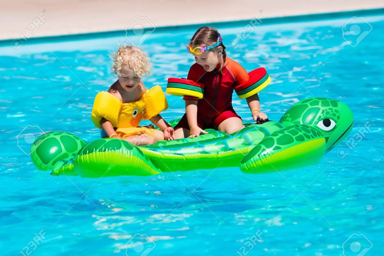 Happy little girl and boy playing in outdoor swimming pool sitting..