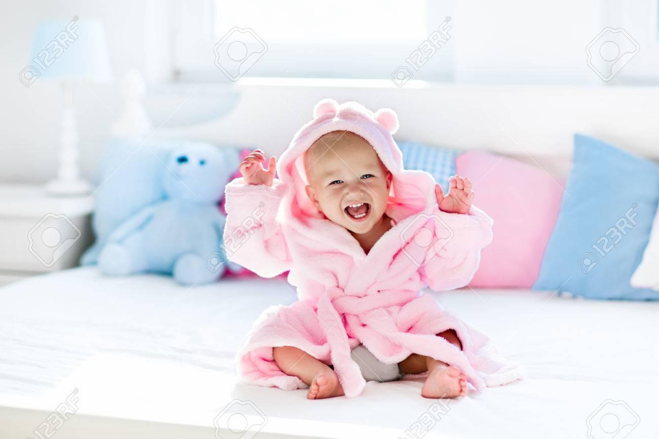 Chambre Enfant Bleu Et Rose cute baby rire heureux dans un peignoir doux après lecture de bain sur lit  blanc avec des oreillers bleu et rose sous le soleil de la chambre des