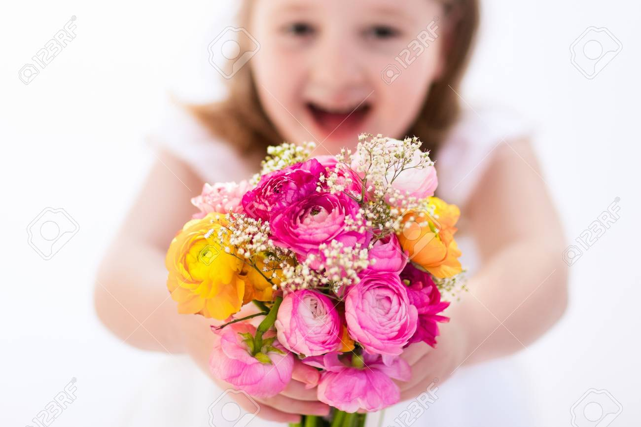 Cute Little Girl In White Dress Holding Ranunculus Flowers Bouquet