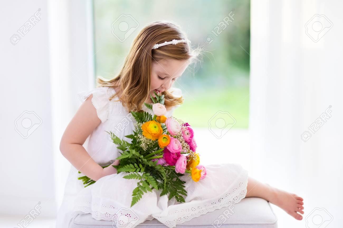 Nettes Kleines Mädchen Im Weißen Kleid Mit Hahnenfuß Blumen Bouquet ...