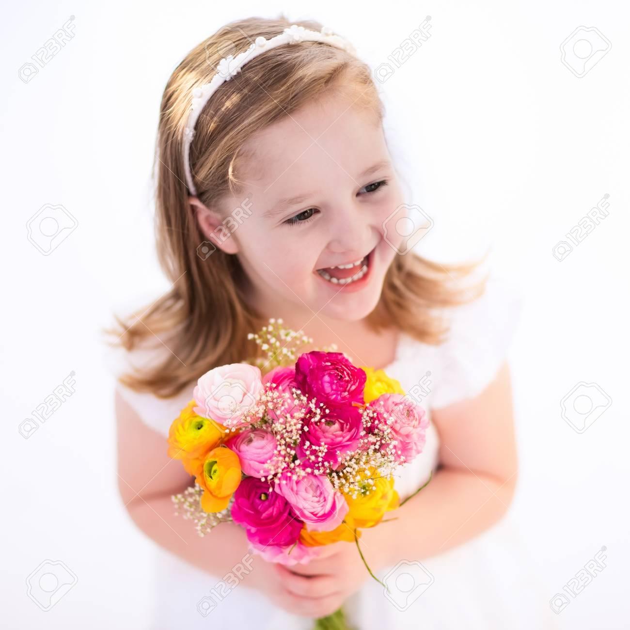 Niña Linda En El Vestido Blanco Que Sostiene Las Flores Del Ramo Del ...