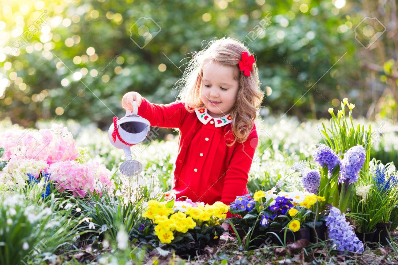 Child Planting Spring Flowers In Sunny Garden Little Girl Gardener