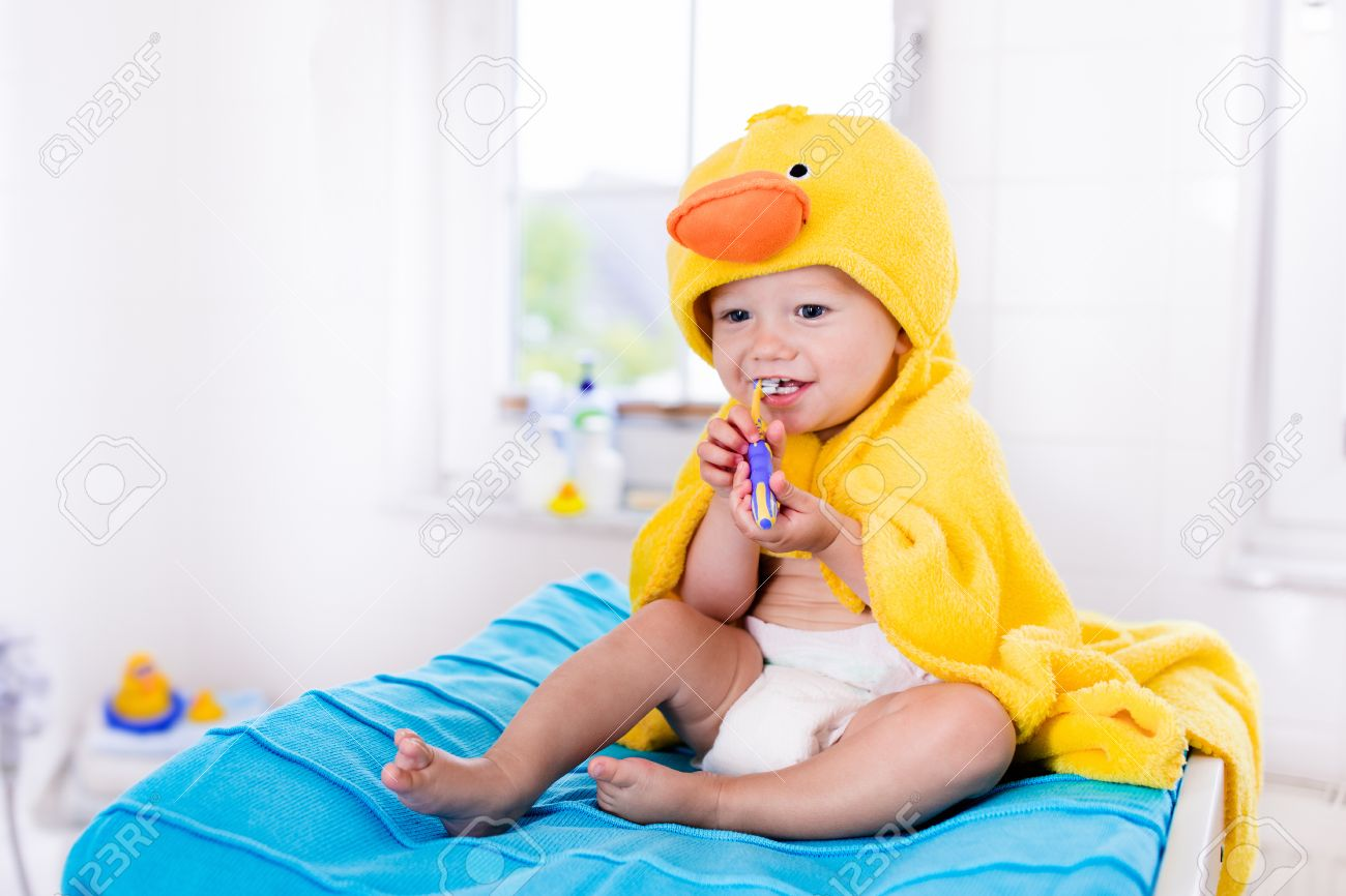 fd143969c Little Baby In Yellow Duck Towel Brushing Teeth On Changing Table ...