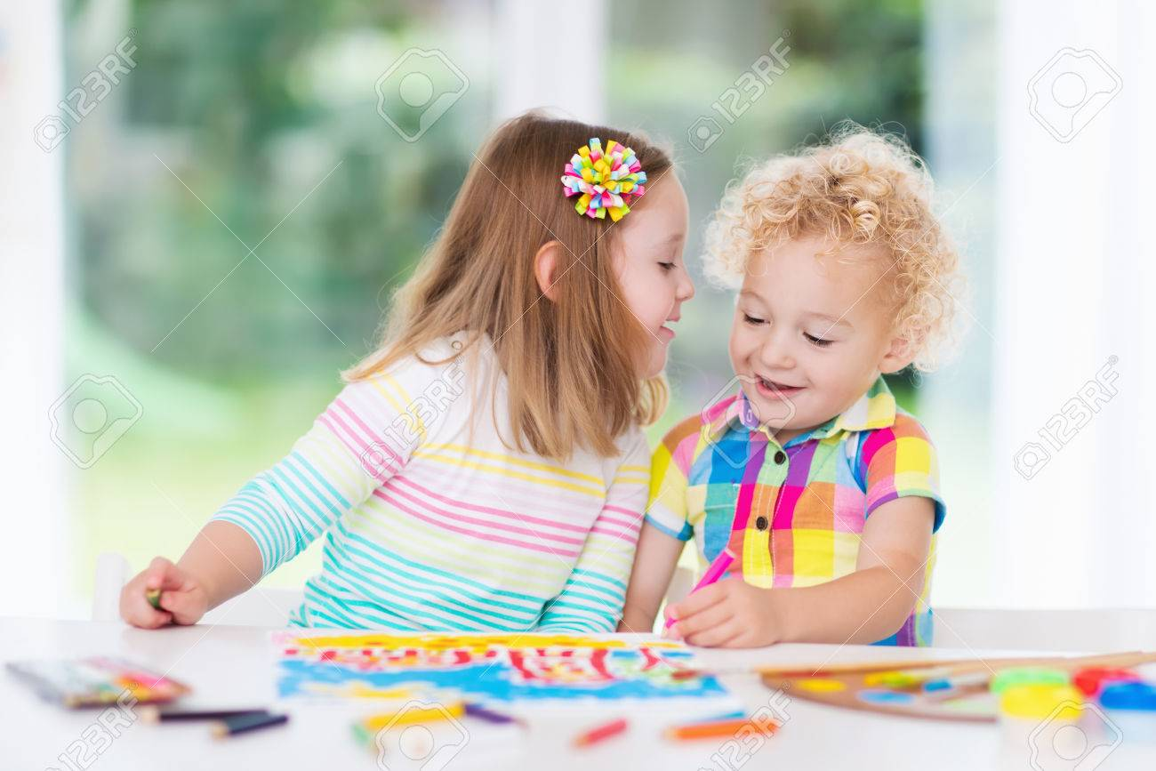 Little Boy And Girl Draw Together In White Room With Window Stock