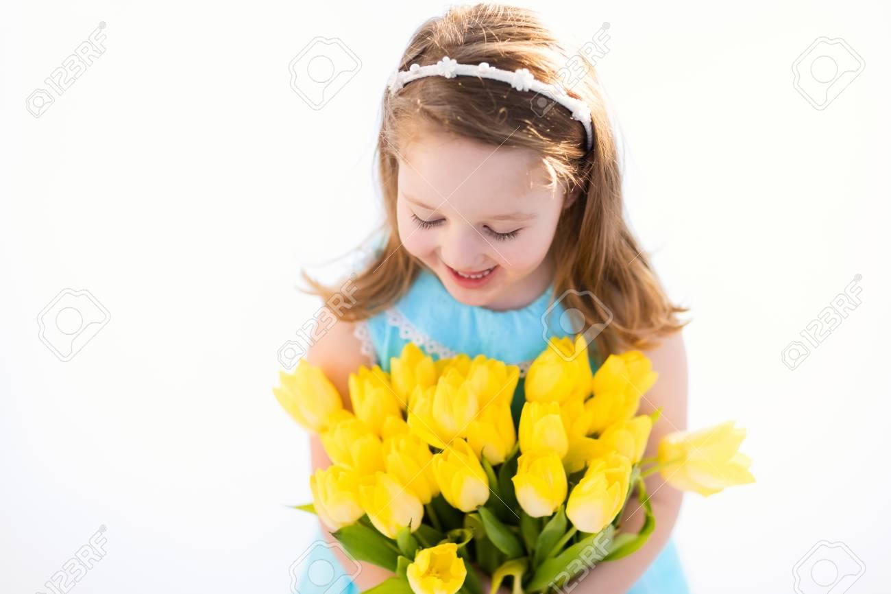 Nettes Kleines Mädchen Im Blauen Kleid Holding Tulpe Blüht ...