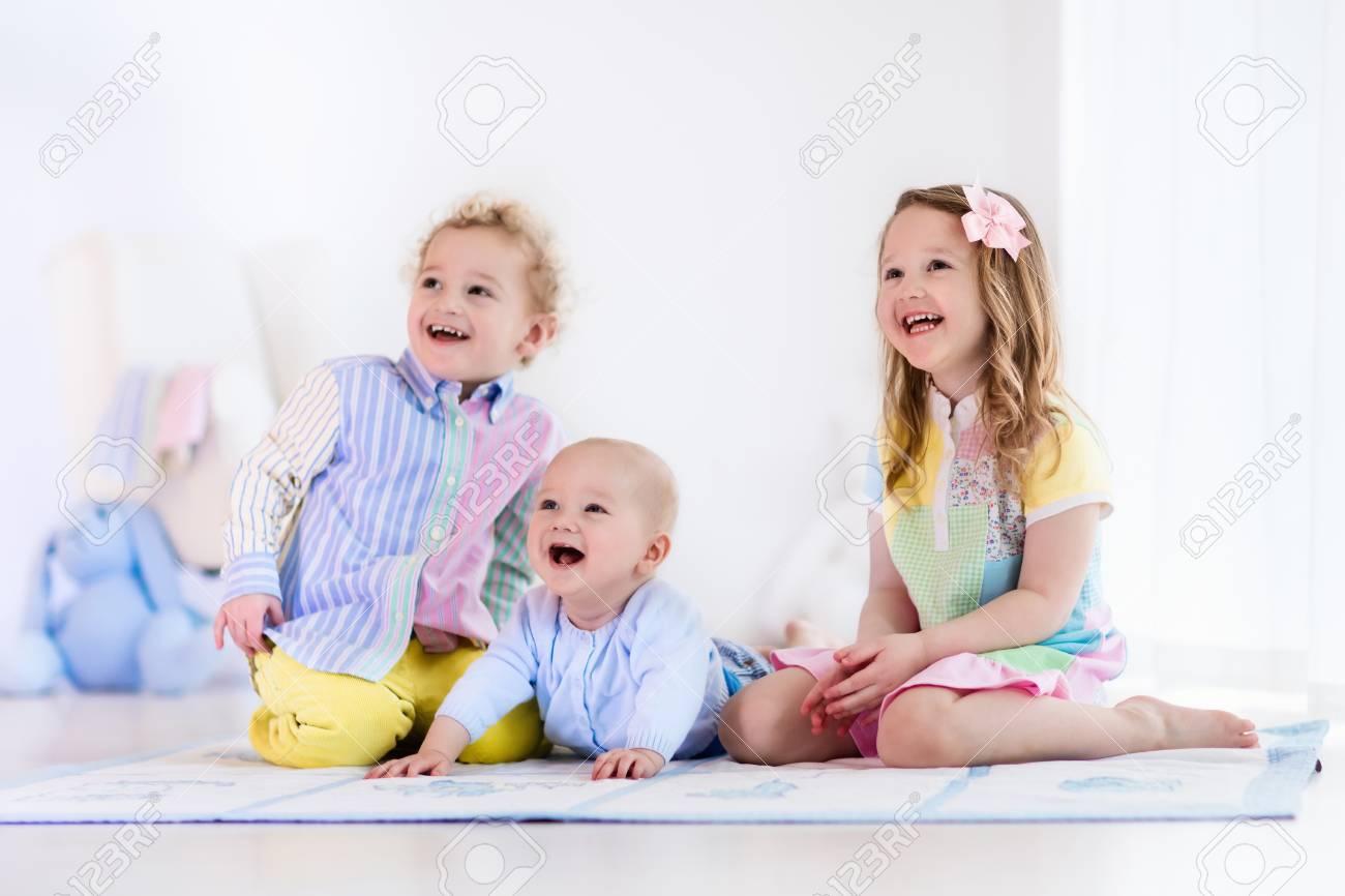 Gruppe Von Drei Kindern In Einem Weissen Schlafzimmer Spielen Kinder