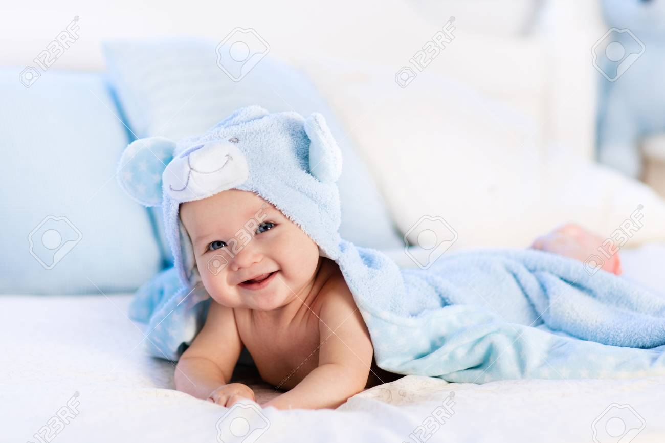 Baby Boy Wearing Diaper And Blue Towel In White Sunny Bedroom ...