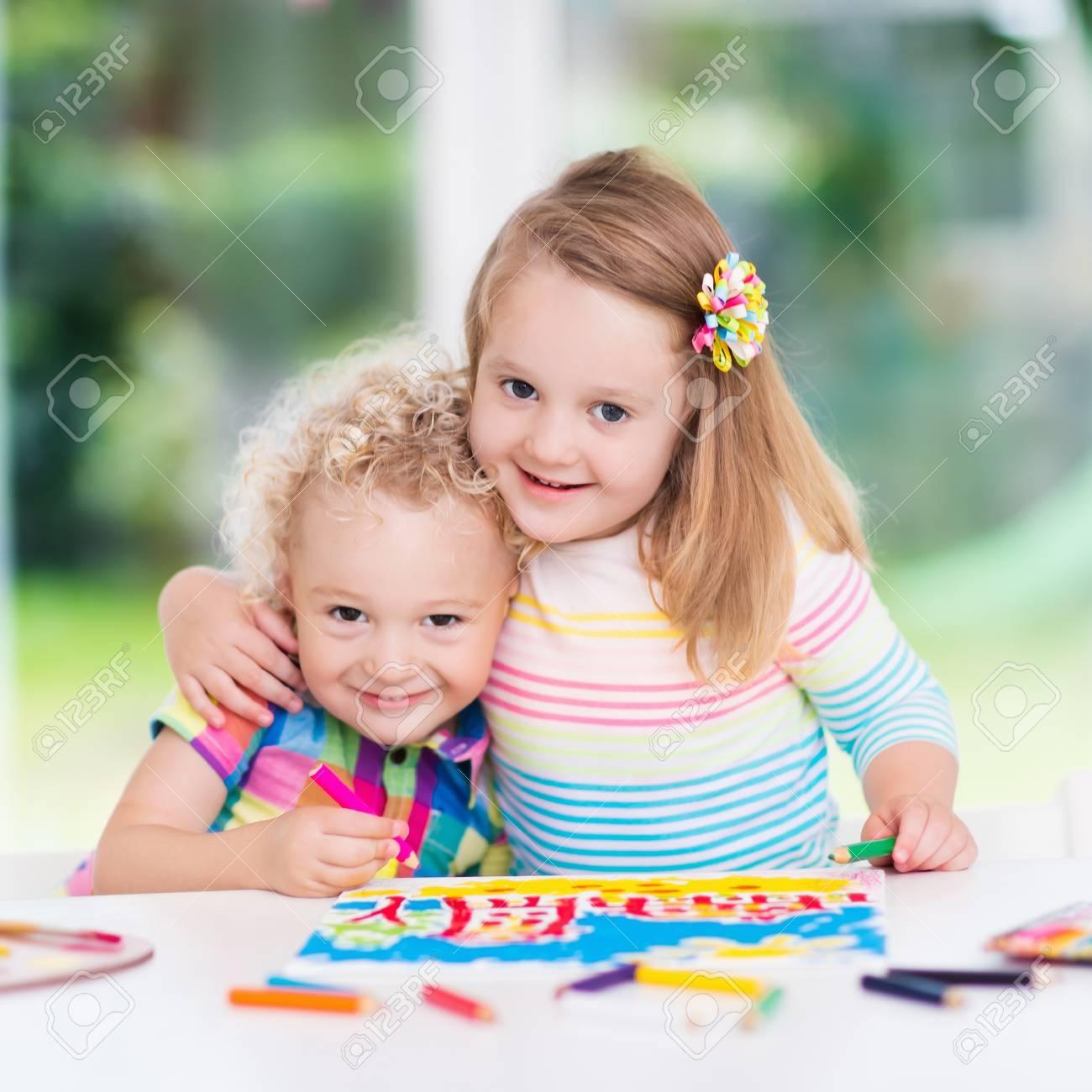 Niño Y Niña Dibujan Juntos En La Sala Blanca Con Ventana. Niños ...