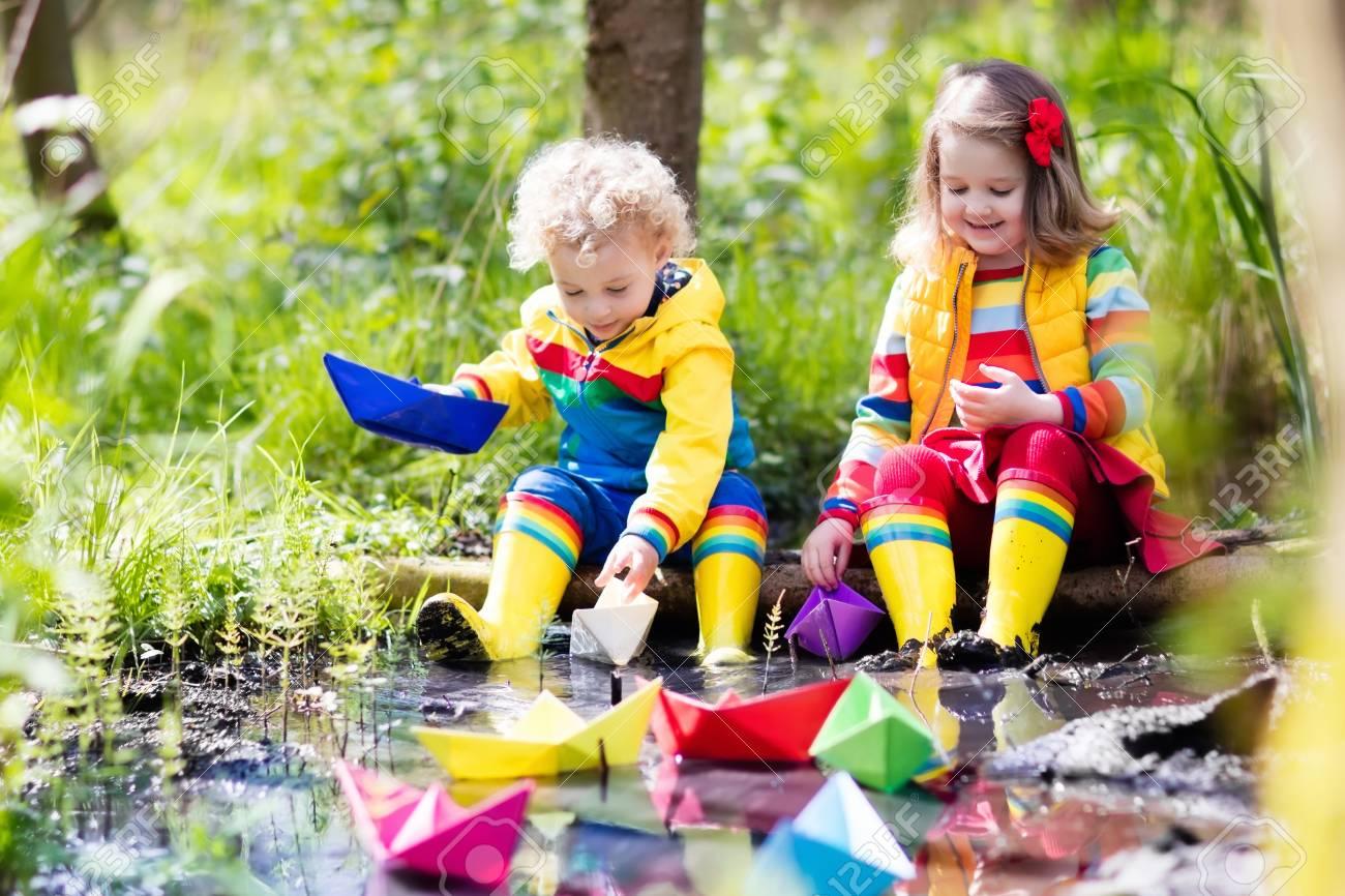 b54456a8956306 Kinder Spielen Mit Bunten Papierbooten In Einem Kleinen Fluss An Einem  Sonnigen Frühlingstag. Kinder Spielen Die Natur Zu Erkunden.
