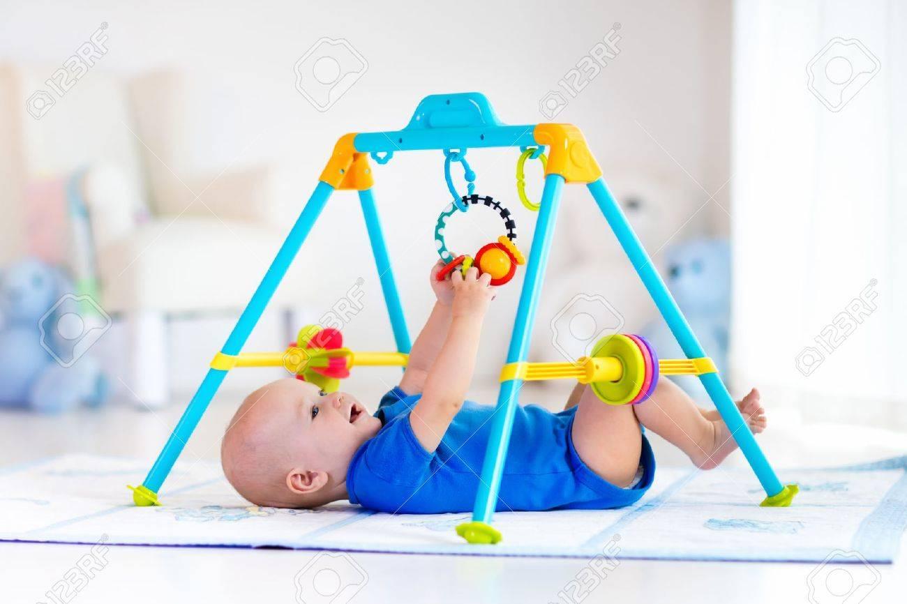 Bebé Lindo En Los Colores Tapete De Juego Y El Gimnasio, Jugando Con ...