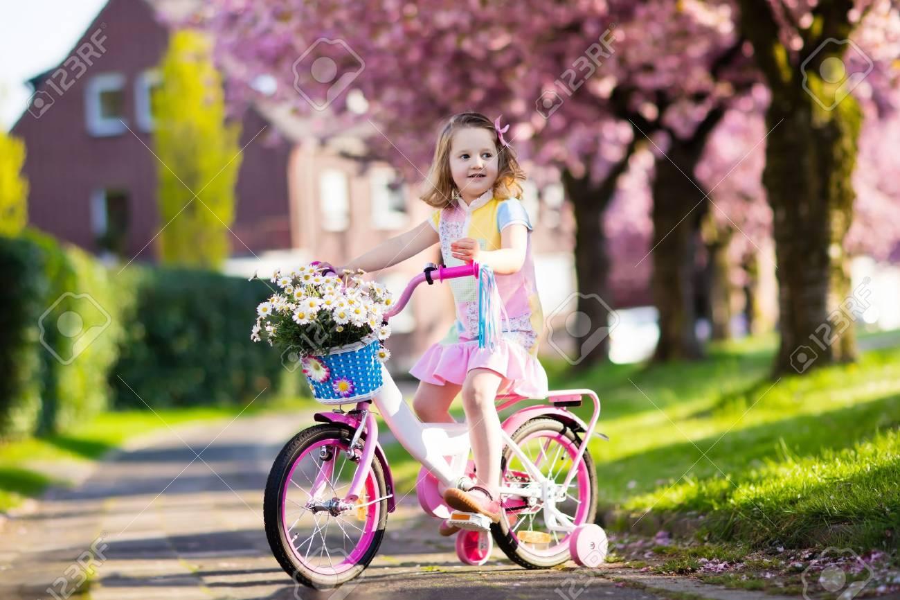 7db0067e920e9 Enfant Chevauchant Un Vélo Sur Une Rue Avec La Floraison Des Cerisiers En  Banlieue. Kid Vélo En Plein Air Dans Le Parc Urbain. Petite Fille à Vélo  Rose.