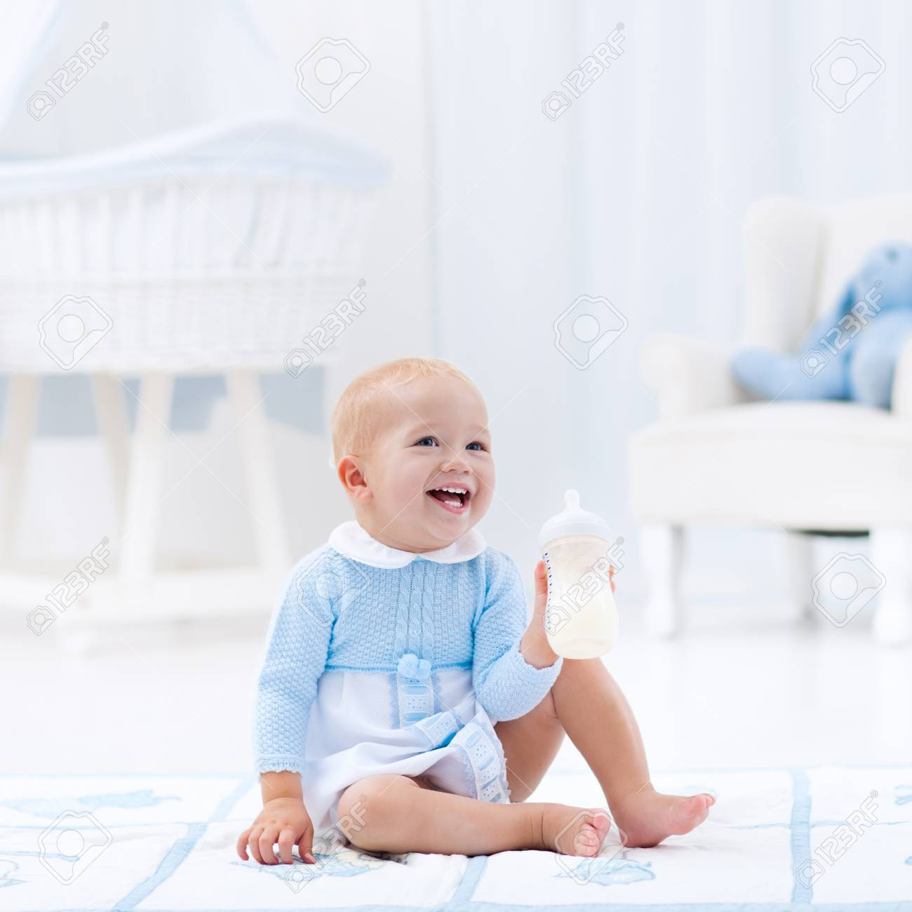 Adorable Baby Boy Playing On A Blue Floor Mat And Drinking Milk