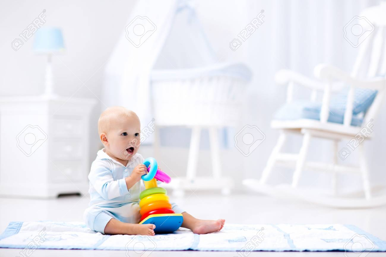 cute baby playing with colorful rainbow toy pyramid sitting on play mat in white sunny bedroom. - 73212224