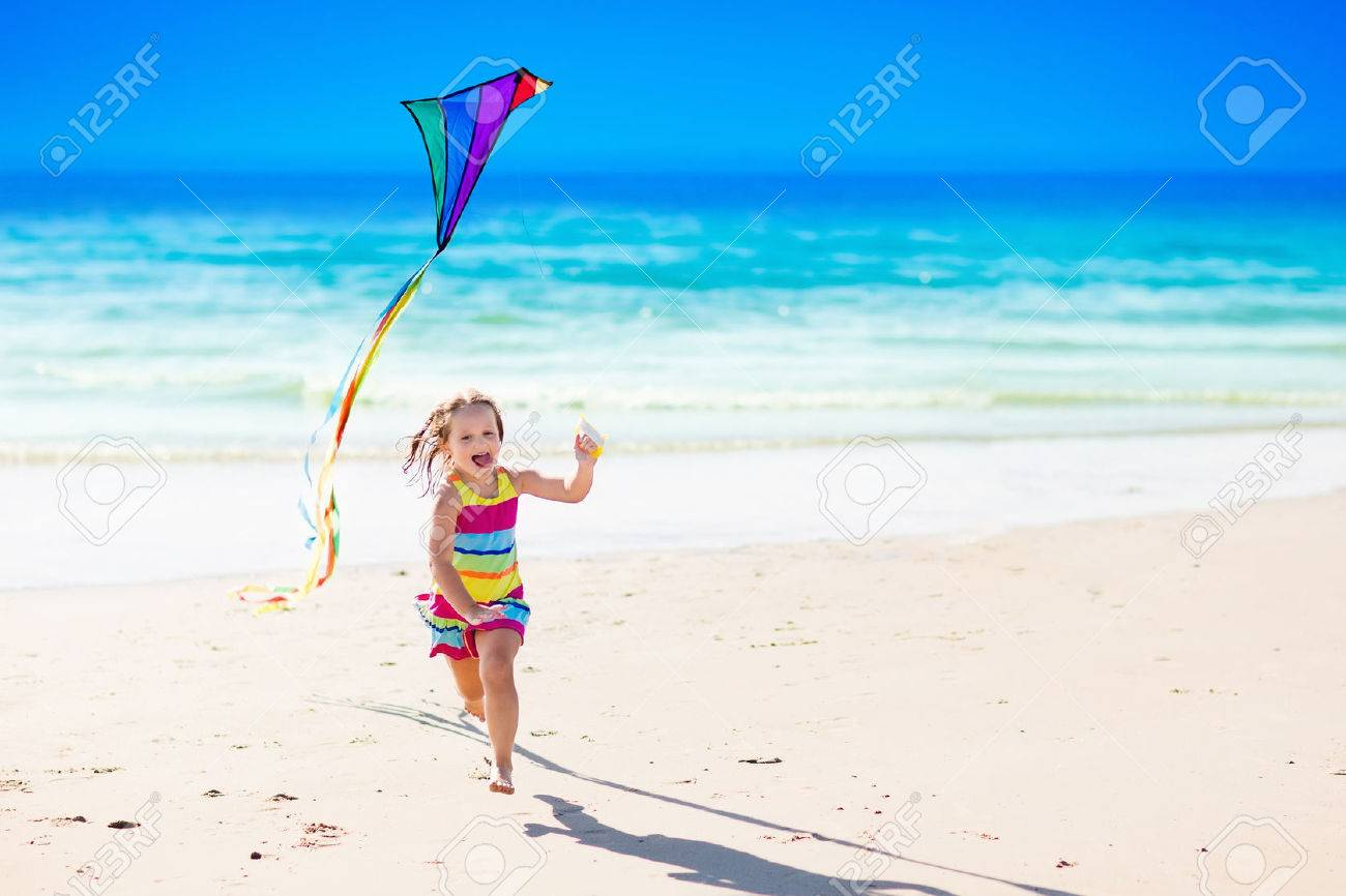 Happy laughing little girl flying a colorful kite running and jumping in sand on beautiful tropical beach during active summer family sea vacation. Kids play on ocean shore. Child with beach toys. - 75450337