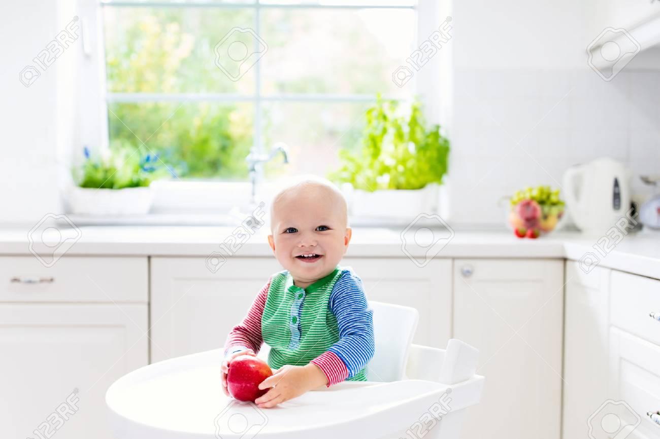 ventana Bebé cocina saludable come y morder con lavabola frutaNiño en la sentado en blanca alta nutrición manzana pequeño silla la soleada la que xrdoeWBC