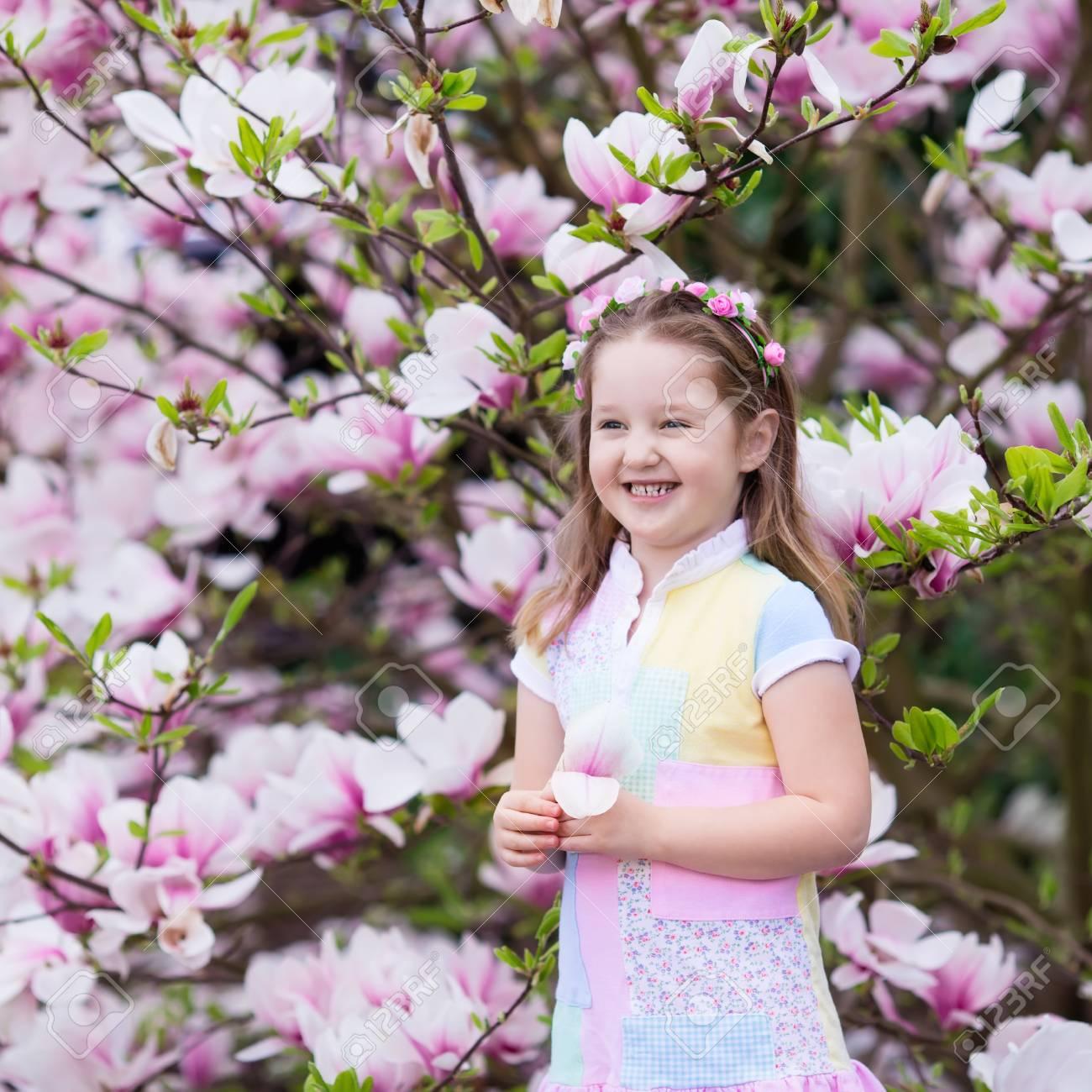 Niña Feliz En El Vestido De Color Pastel Y Una Corona De Flores Juega Bajo El árbol De Magnolia Rosa Recogiendo Flores Grandes En Jardín Floreciente