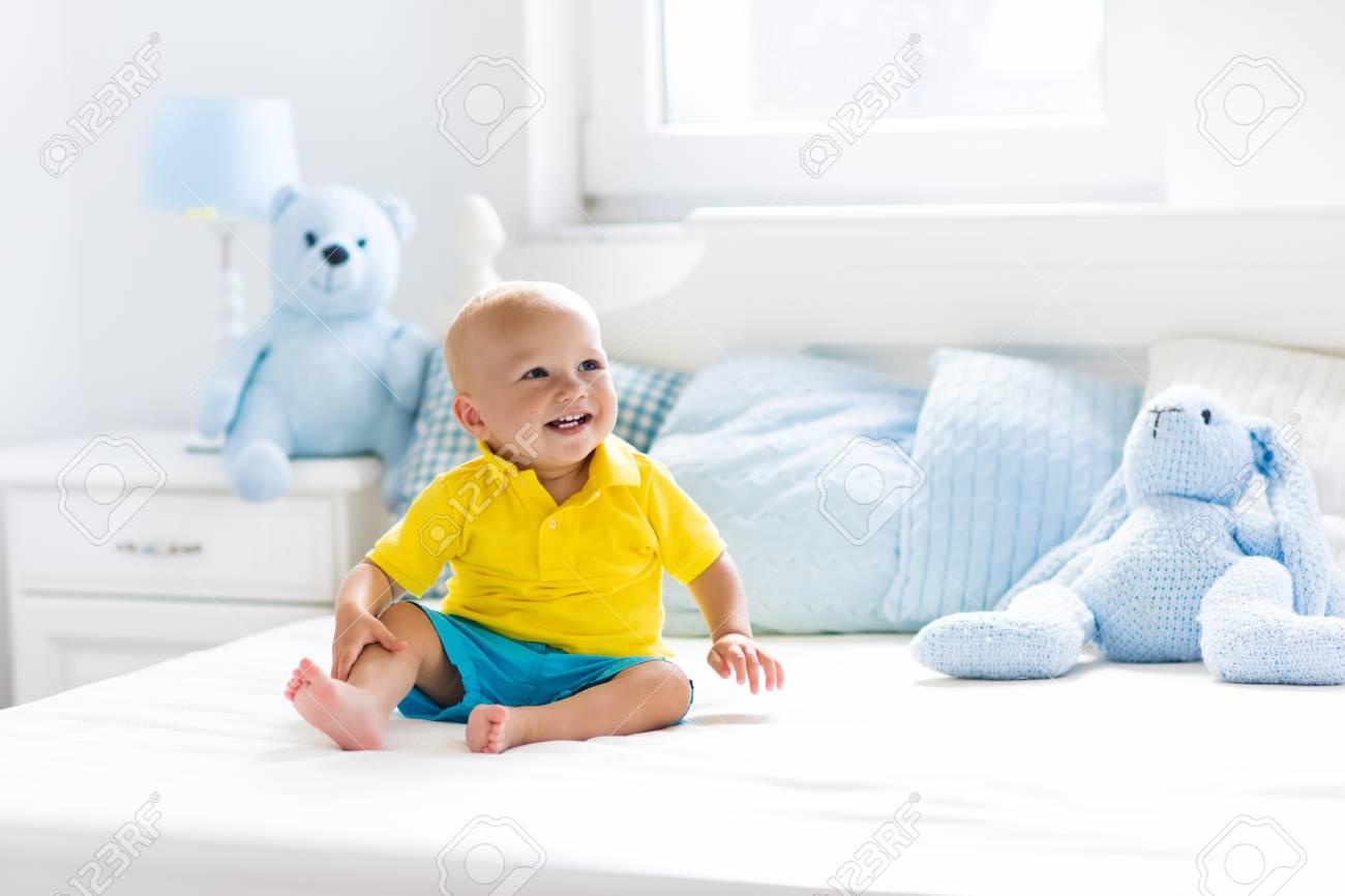 Baby Spielt Auf Bett Der Eltern Nette Lustige Kleine Junge Lernen In Weiss Sonnigen Kinderzimmer