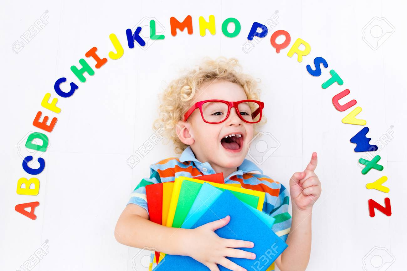 Happy Preschool Child Learning To Read And Write Playing With