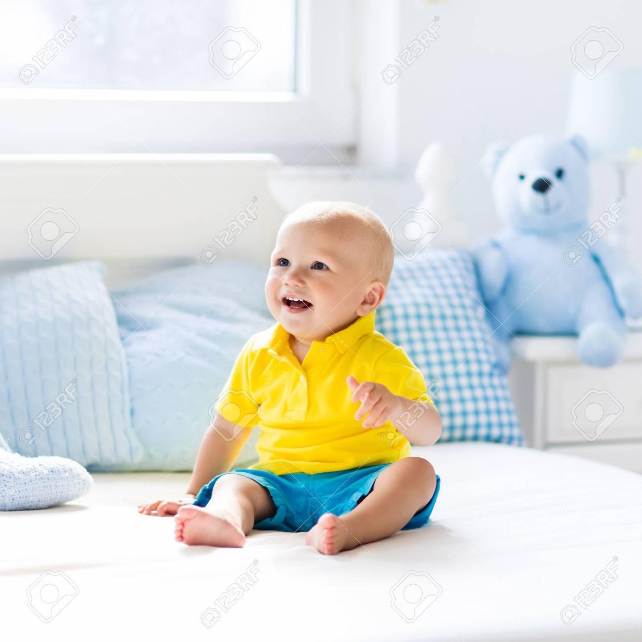 赤ちゃんは 両親と同じベッドで遊ぶ かわいい面白い男の子白日当たりの良い保育園でクロールする学習します 乳児と幼児はルーム インテリアです ベッド 子供のためのおもちゃ 子供たちは家庭で遊ぶ 赤ちゃんのベッドルーム の写真素材 画像素材 Image
