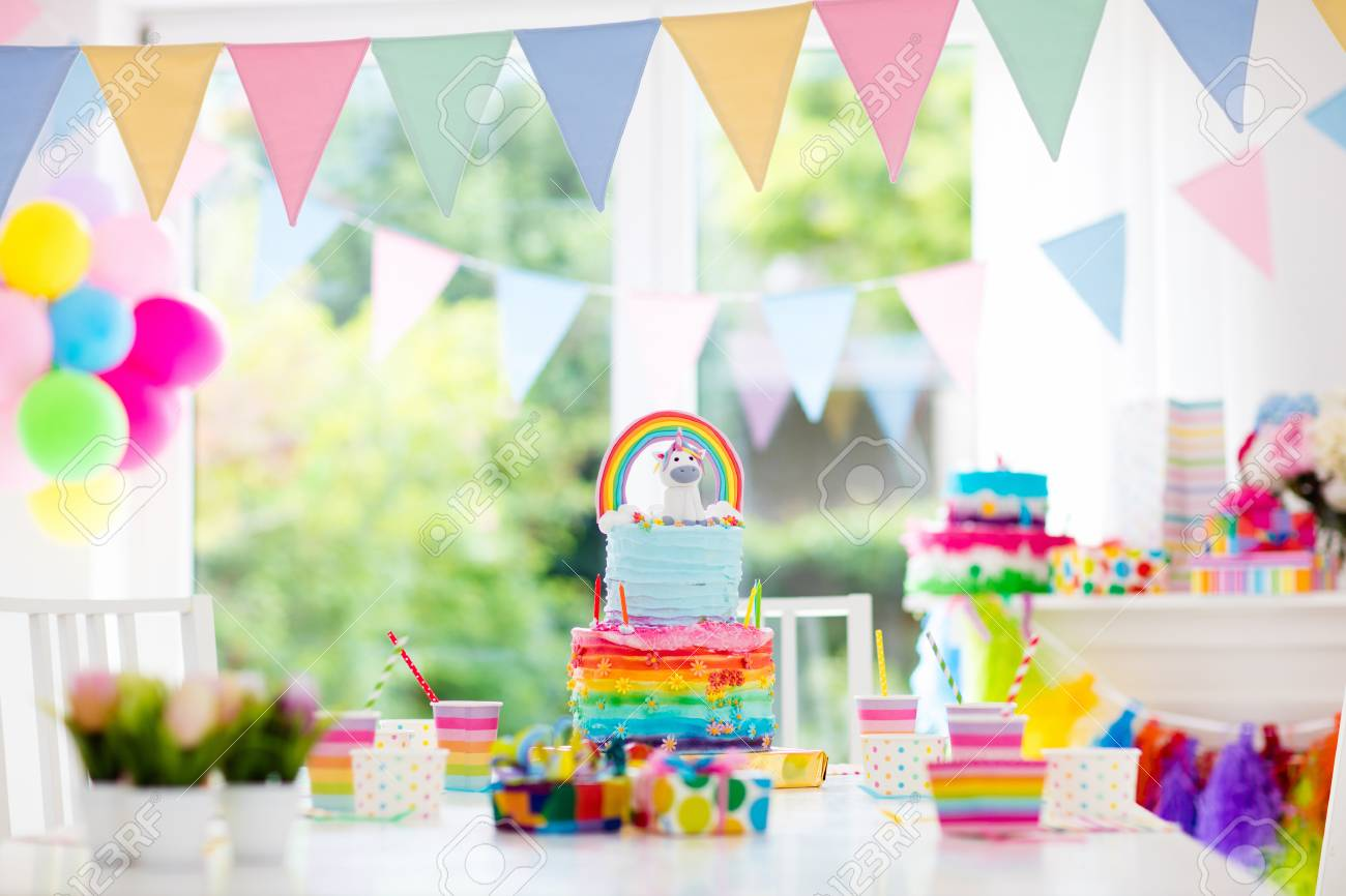 Kids birthday party decoration and cake. Decorated table for child birthday celebration. Rainbow unicorn cake for little girl. Room with festive balloons, colorful banners in baby pastel color. - 78956893