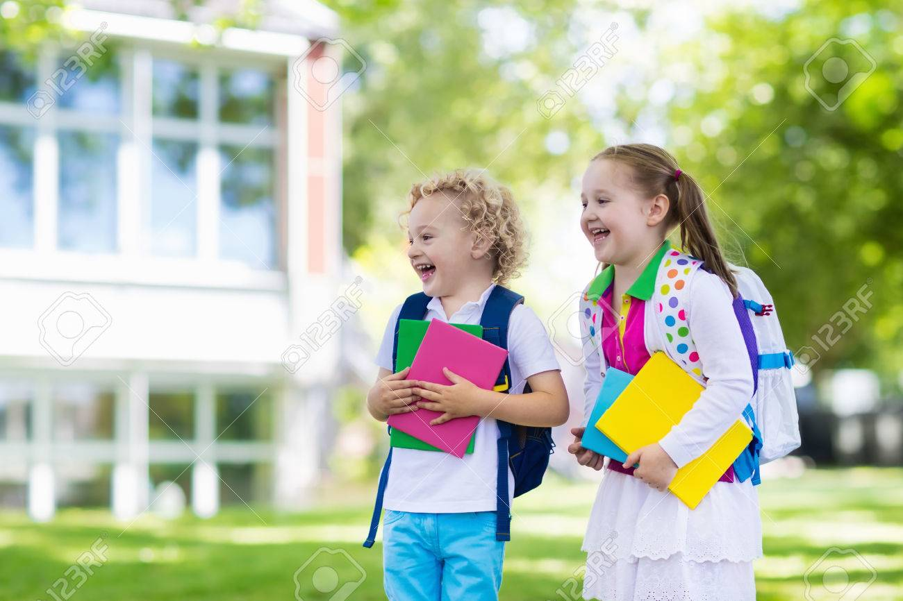 Children go back to school. Start of new school year after summer vacation.  Boy and girl with backpack and books on first school day. Beginning of  class. 4ebd13cc98dee