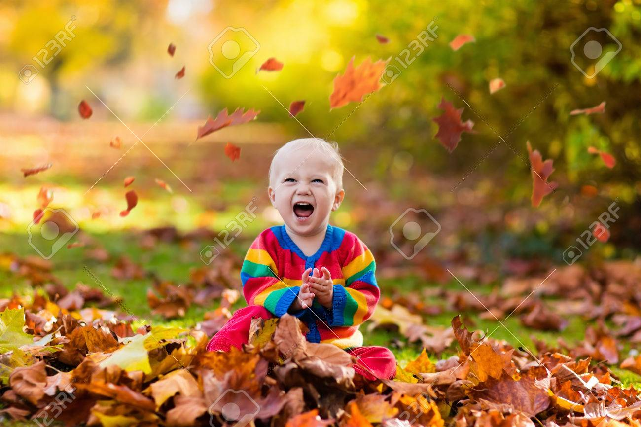 Kids play in autumn park children throwing yellow and red leaves baby with oak