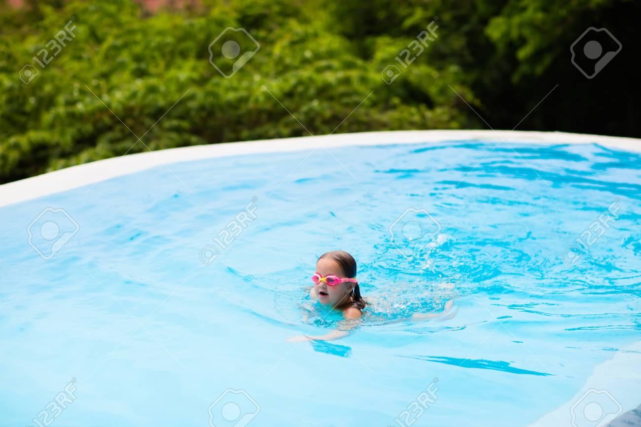 Kind Mit Schutzbrille Im Schwimmbad. Kleines Mädchen Lernt Zu Schwimmen Und  Tauchen Im Freibad Tropischen