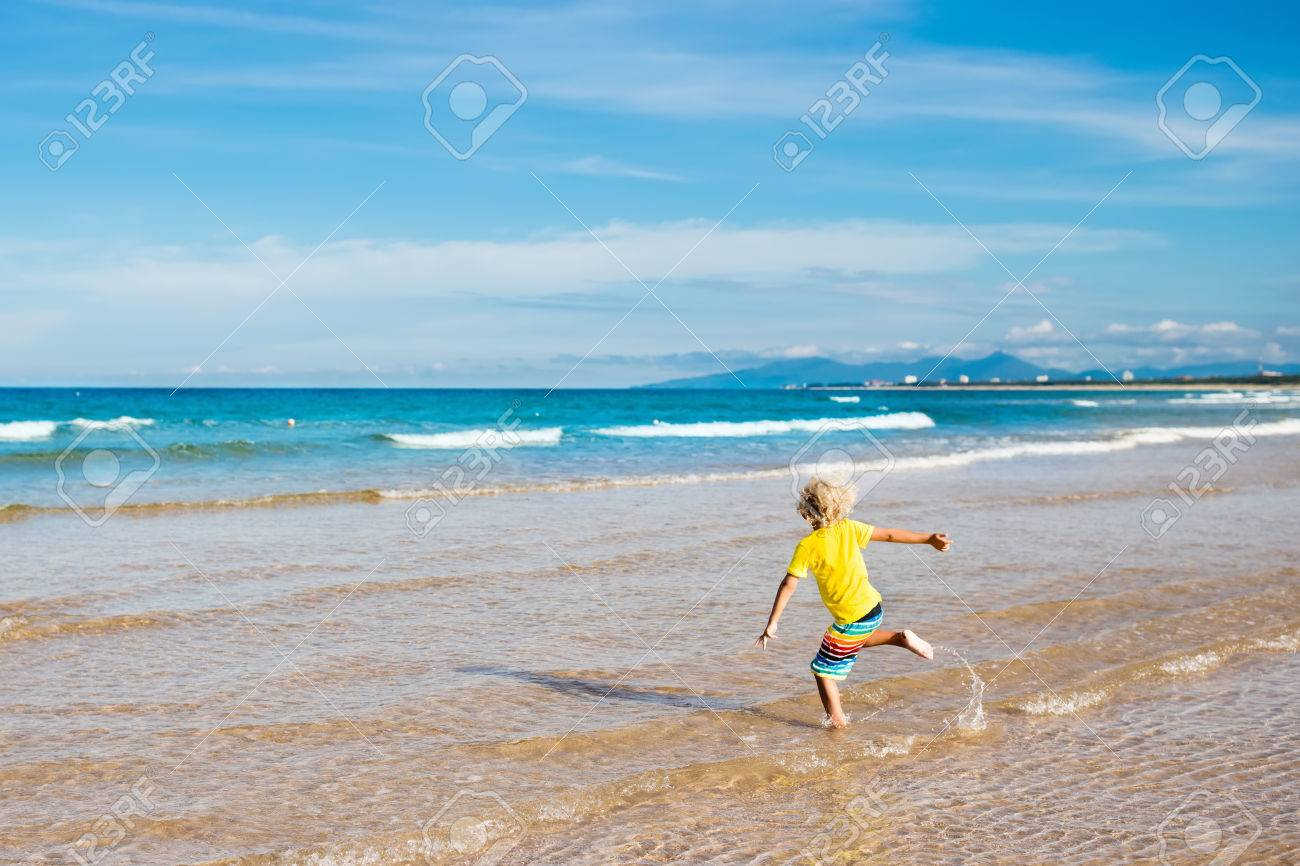 Child On Beautiful Beach Little Boy Running And Jumping At Sea Shore Ocean Vacation