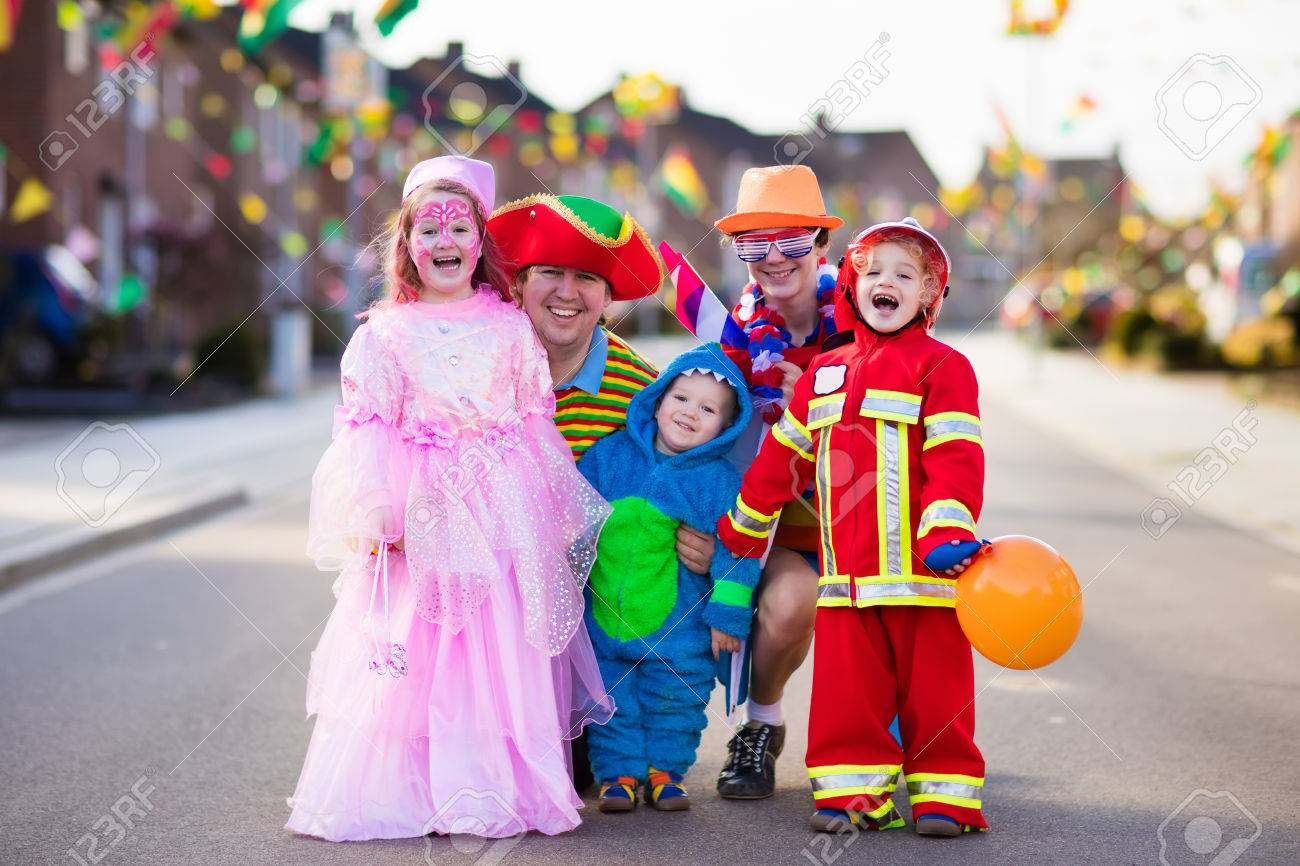 Kids and parents on Halloween trick or treat. Family in Halloween costumes with candy bags walking in decorated street trick or treating. Baby and preschooler celebrating carnival. Child costume. - 85529817
