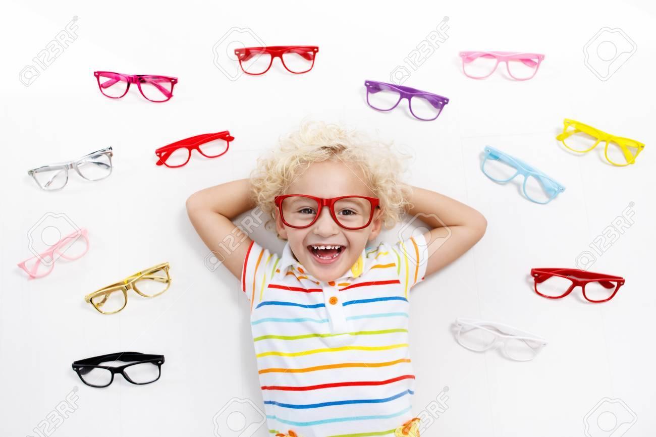 6b9744dfd8 Child at eye sight test. Little kid selecting glasses at optician store. Eyesight  measurement