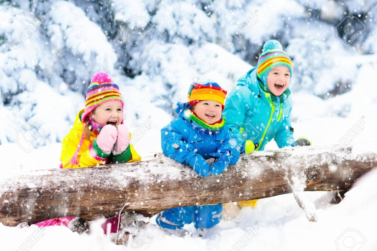 Kids playing in snow. Children play outdoors on snowy winter day. Boy and girl catching snowflakes in snowfall storm. Brother and sister throwing snow balls. Family Christmas vacation activity. - 87527757