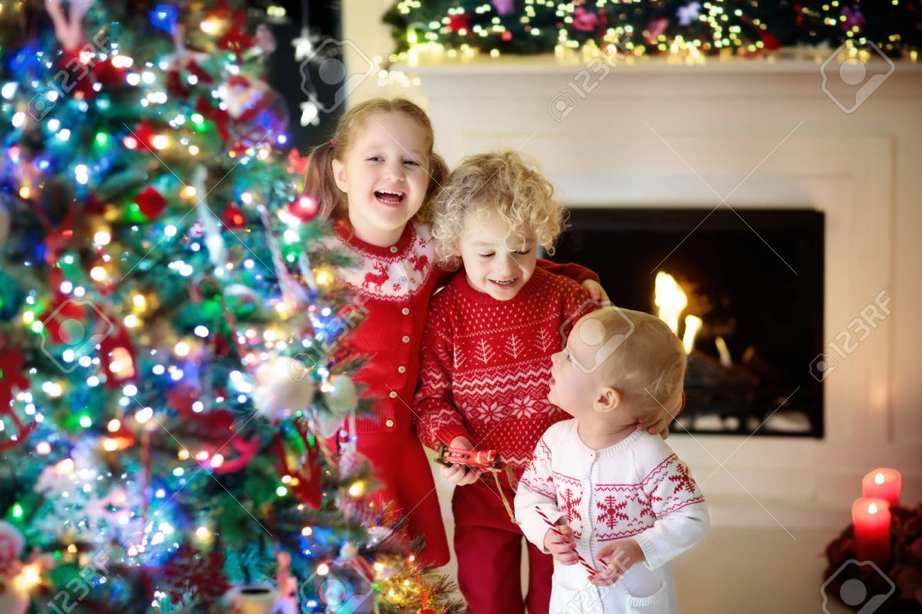 Children At Christmas Tree And Fireplace On Xmas Eve. Family.. Stock ...
