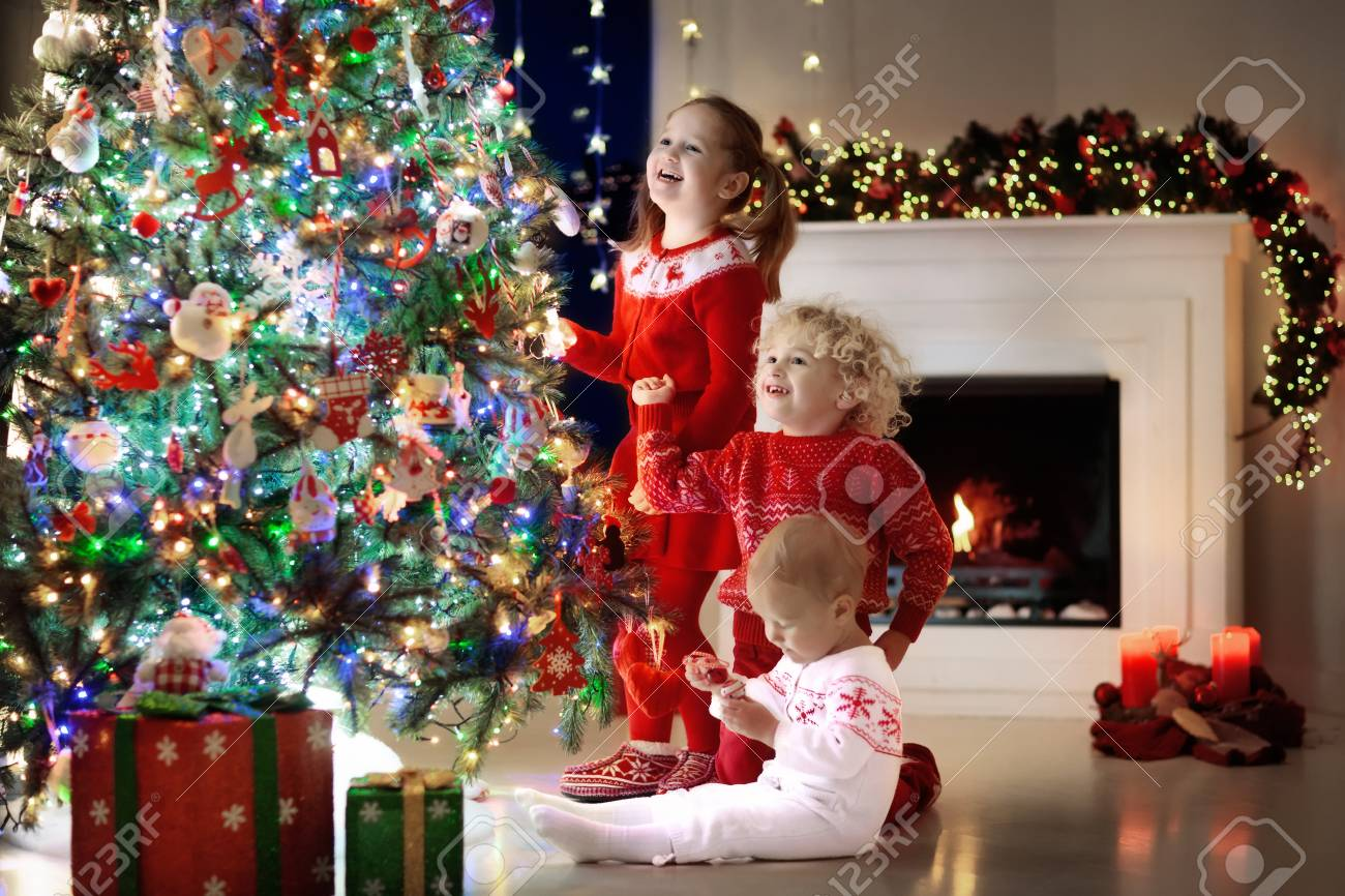 Children At Christmas Tree And Fireplace On Xmas Eve Family Stock Photo Picture And Royalty Free Image Image 88562674
