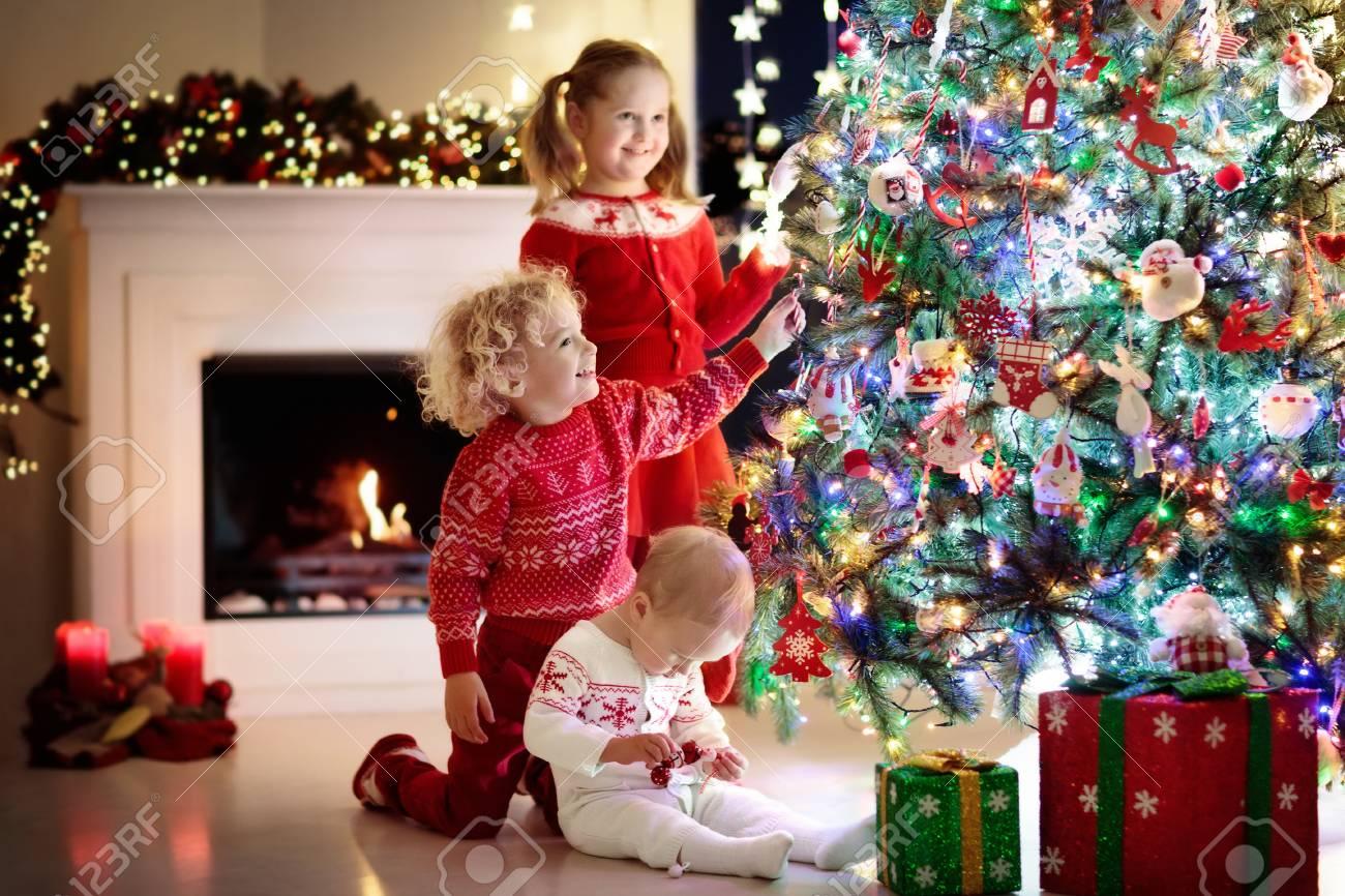 Ninos En El Arbol De Navidad Y Chimenea En La Vispera De Navidad