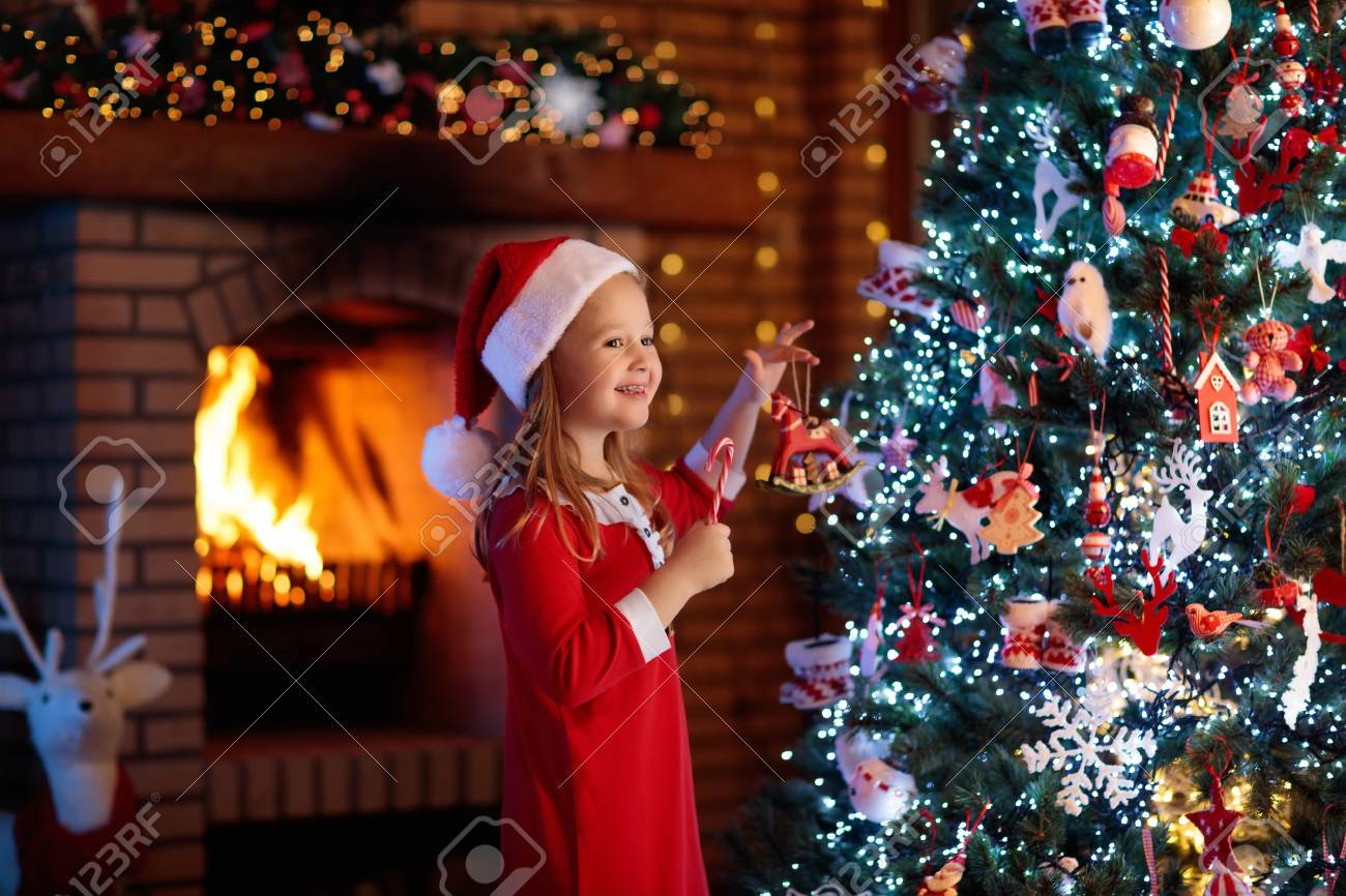 Child At Christmas Tree And Fireplace On Xmas Eve Family With