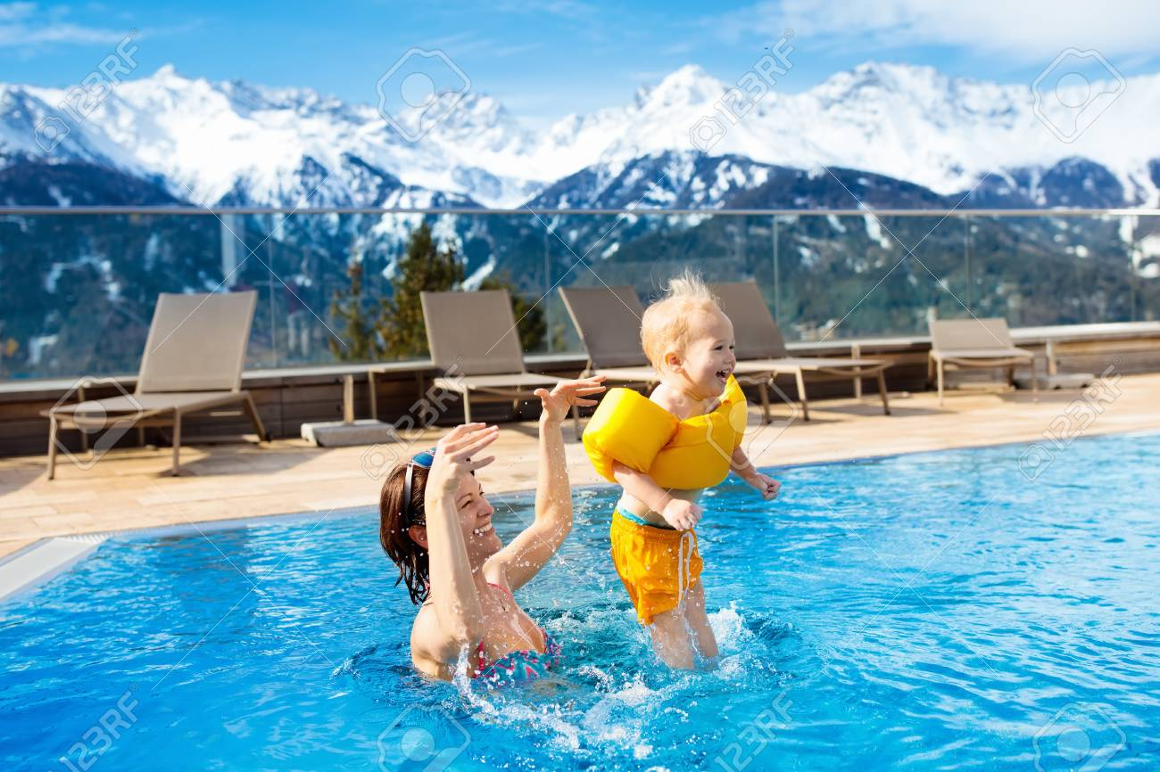 Mother And Baby Play In Outdoor Swimming Pool Of Luxury Spa Alpine ...