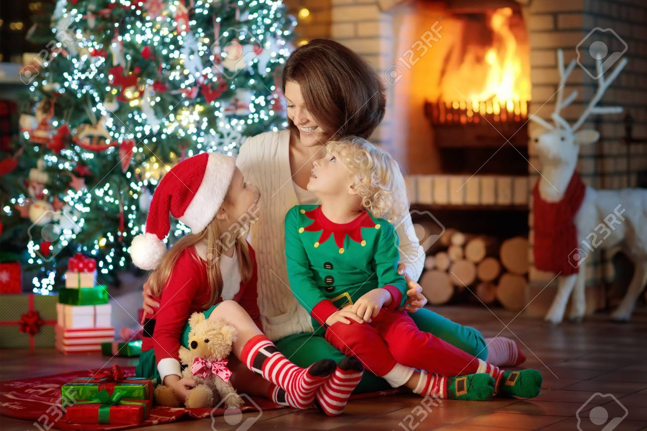 family with kids at christmas tree and fireplace mother and children opening gifts at fire