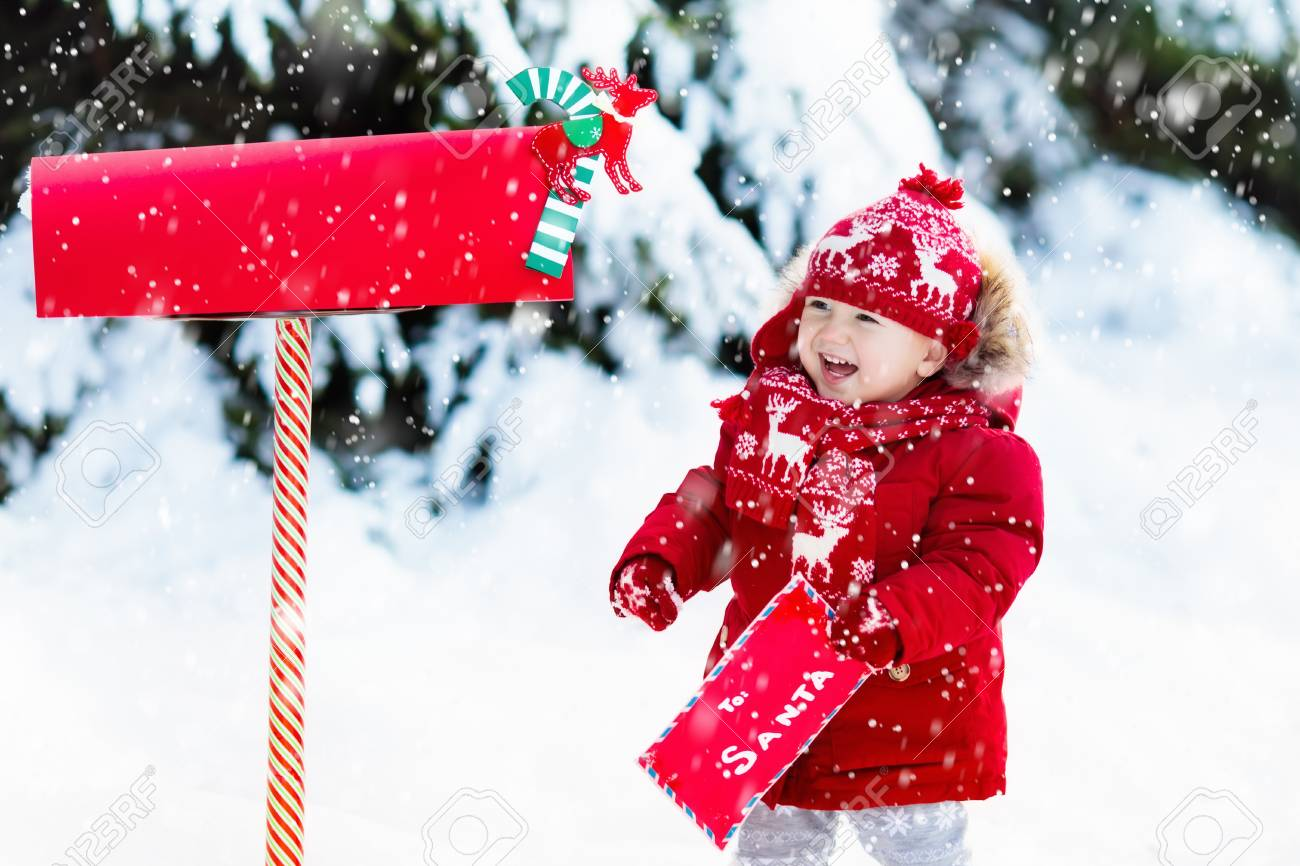 a9716583fa3ab Happy child in knitted reindeer hat and scarf holding letter to Santa with  Christmas presents wish list at red mail box in snow under Xmas tree in  winter ...