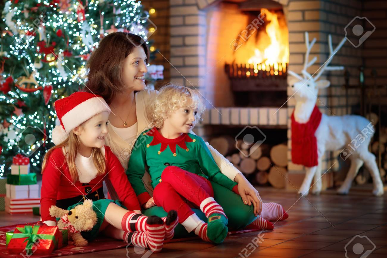 Family With Kids At Christmas Tree And Fireplace. Mother And.. Stock ...