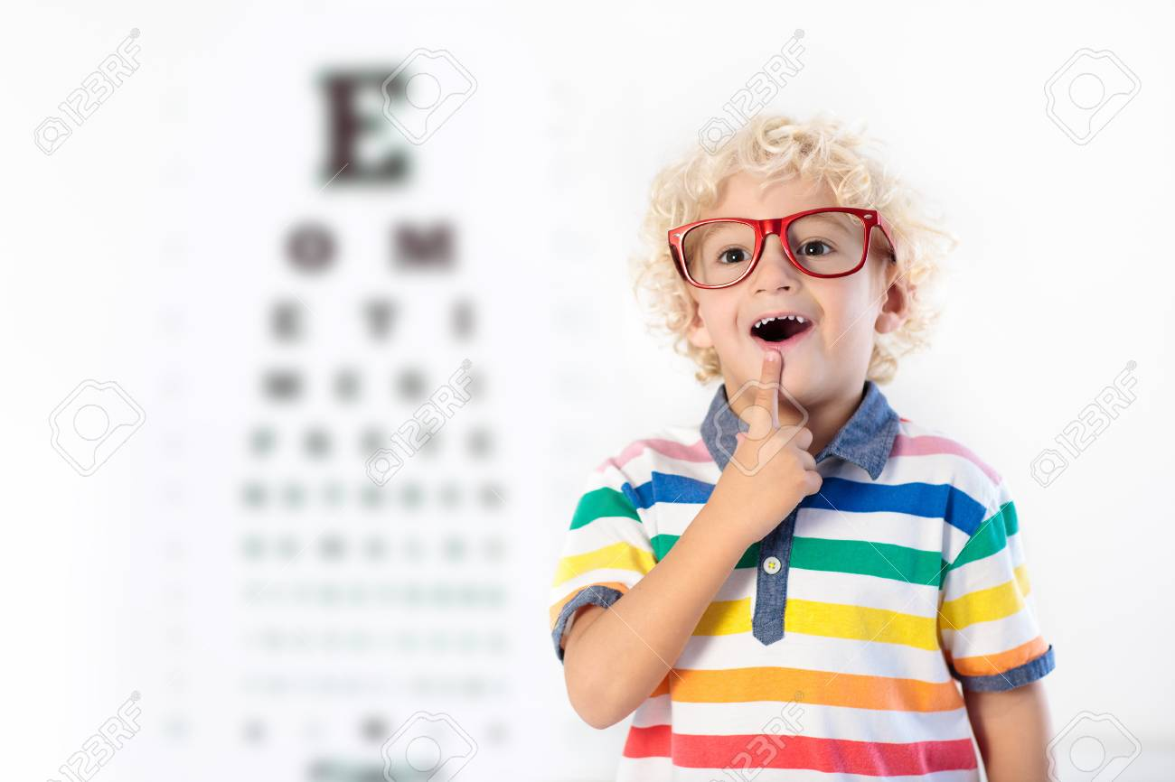Child At Eye Sight Test Little Kid Selecting Glasses At Optician